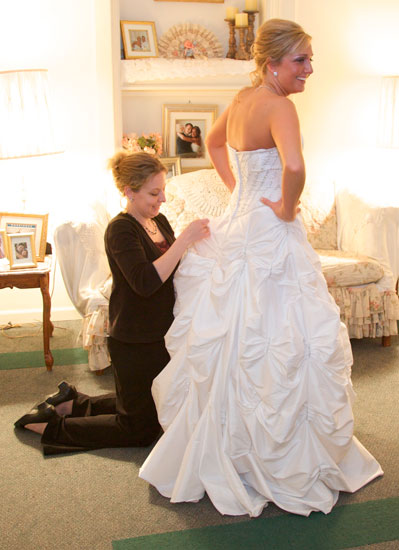 Tiffany sews up Logan's bustle in Hamilton's VIP room. Copyright Warmowski Photography.
