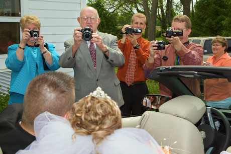 Retired wedding photographer joins in with the rest of the family as Kristen and Joel Buchanan pose in their get-away car.