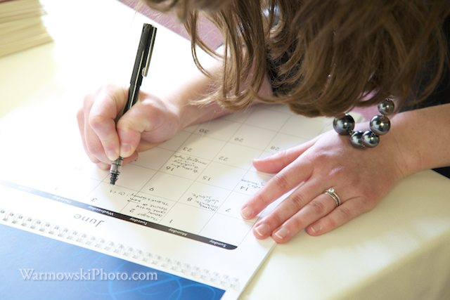 Guests write in birthdays, anniversaries and other special dates on a calendar at Genny & Ben Six's reception.