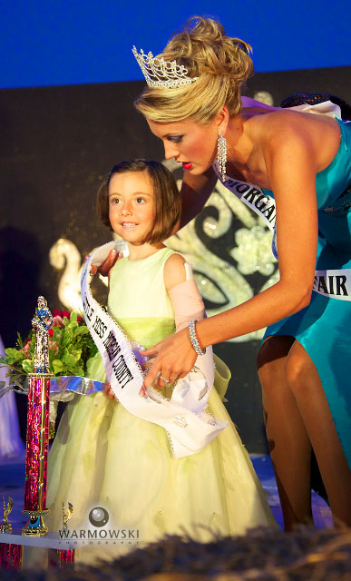 Grace Newman gets her 2010 Little Miss sash from 2009 Queen Alyssa Jackson during the Morgan County Fair Pageant Tuesday 6 July in Jacksonville.