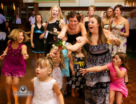 Bouquet toss, a one-handed catch with beer spilling from cup onto head of little girl; wedding images by Warmowski Photography