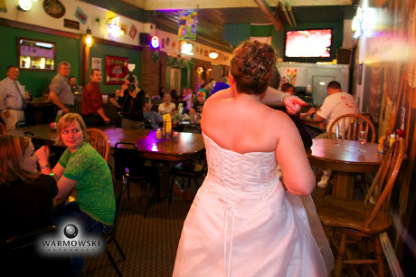Bride in bar to get lost male guests for garter toss; wedding photos by Warmowski Photography