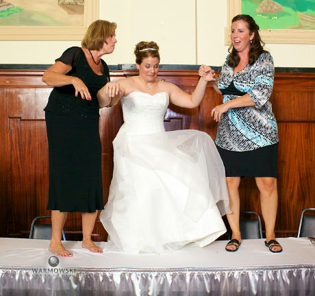 Reluctant bride pulled onto table at wedding; wedding photos by Warmowski Photography