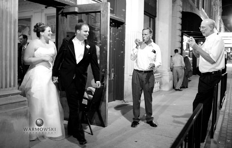 Bride & groom leave reception hall, guests blow bubbles, walk away into night; wedding photos by WarmowskiPhotography.com