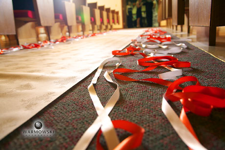 White & orange ribbons along aisle runner in church for wedding, image by Warmowski Photography
