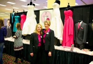 Girls in White Satin in front of their bride dress booth at wedding show