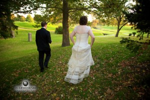 Bride and groom from behind walk in park