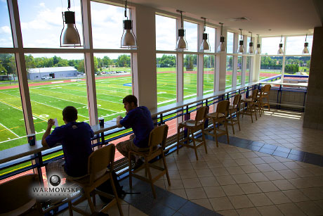Students behind table looking over football field at Illinois College - WarmowskIPhotography.com