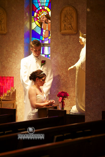 Monica kneels before the Blessed Mother after presenting her flowers. Monica's brother and Man-of-Honor, Anthony, sang Ave Maria with his a capella group. Monica is holding a wedding rosary which has beads made of flowers from the recent funeral of her late grandmother.