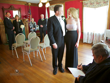 Bride and groom look at each other while wedding license signed by judge - Warmowski Photography