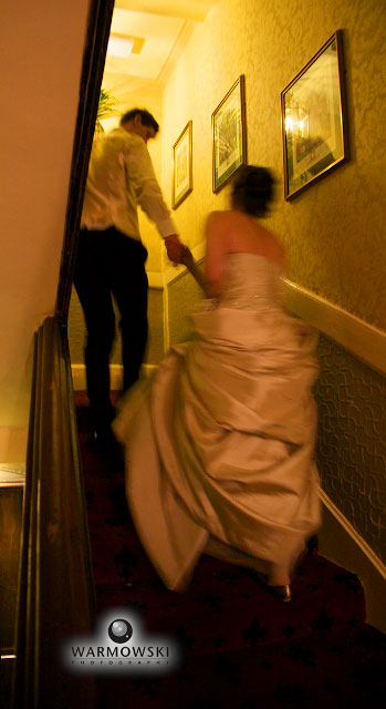 Bride & groom go upstairs to bridal suite. WarmowskiPhoto.com