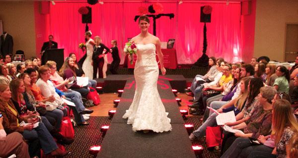 Bride model wedding dress walks down runway, red LED uplighting in background. http://www.warmowskiphoto.com