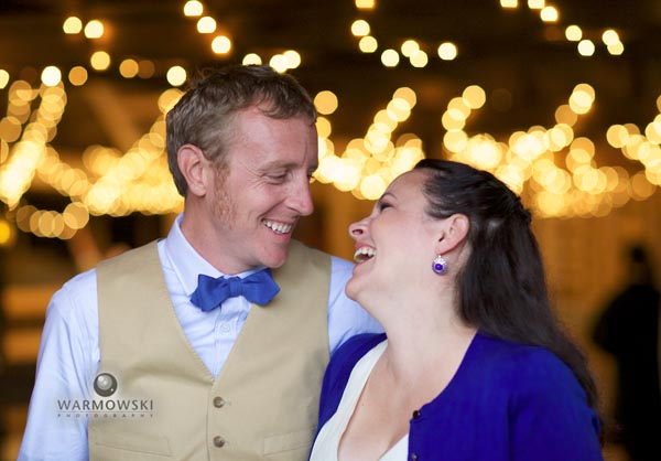 Katie & Zach in front of strings of lights used to illuminate barn.