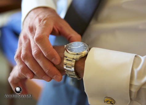 Daniel checks the time, getting ready at the Inns of Geneva National. Wedding photography by Steve & Tiffany Warmowski