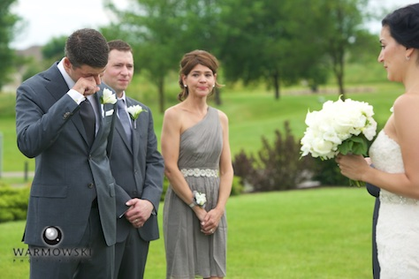 Daniel reacts as Emi comes down the aisle. Wedding photography by Steve & Tiffany Warmowski