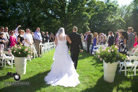 Amy walks down the aisle with her father at her wedding in rural Springfield. Amy's parents Mark and Susan gave the couple a beautiful outdoor wedding right in their yard. Wedding photography by Tiffany & Steve of Warmowski Photography.