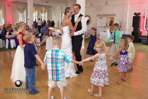 DJ Troy Armstrong loves to work children into the events of the day, including encircling Amber & Ryan during their first dance. Wedding photography by Steve & Tiffany Warmowski