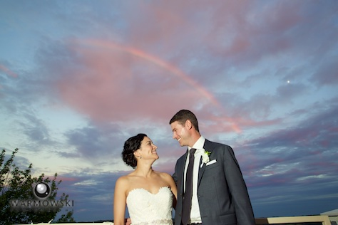 A sun shower at sunset makes for a beautiful rainbow, and the bride and groom take a break from greeting guests for a portrait on the balcony, reception at Geneva National Golf Club. Wedding photography by Steve & Tiffany Warmowski