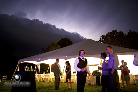 A storm front made guests choose to stick with the meal tent, the party tent or inside the house. Wedding of Amy & Brad at the bride's family home in rural Springfield. Wedding photography by Tiffany & Steve of Warmowski Photography.